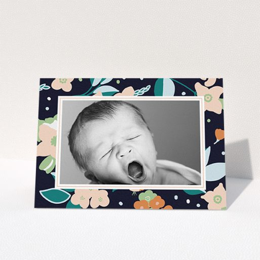 """A baby card design titled """"Bedtime Garden"""". It is an A6 card in a landscape orientation. It is a photographic baby card with room for 1 photo. """"Bedtime Garden"""" is available as a folded card, with tones of navy blue, pink and orange."""