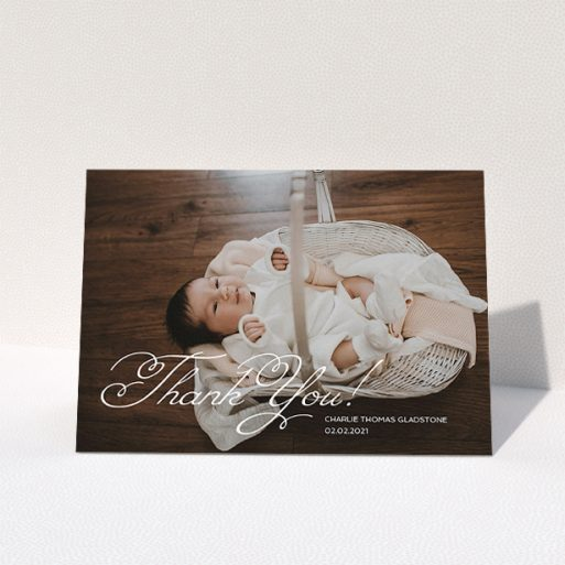 """A baby thank you card called """"Flourished Thank You"""". It is an A5 card in a landscape orientation. It is a photographic baby thank you card with room for 1 photo. """"Flourished Thank You"""" is available as a folded card, with mainly white colouring."""