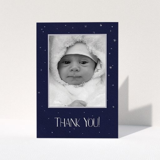 """A christening thank you card template titled """"Written in the Stars"""". It is an A6 card in a portrait orientation. It is a photographic christening thank you card with room for 1 photo. """"Written in the Stars"""" is available as a folded card, with tones of dark blue, white and silver."""