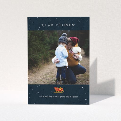 """A custom christmas card design called """"Glad Tidings with Sleigh"""". It is an A5 card in a portrait orientation. It is a photographic custom christmas card with room for 1 photo. """"Glad Tidings with Sleigh"""" is available as a folded card, with tones of blue and white."""