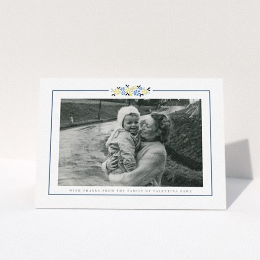 """A funeral thank you card called """"Remembered in flowers"""". It is an A6 card in a landscape orientation. It is a photographic funeral thank you card with room for 1 photo. """"Remembered in flowers"""" is available as a folded card, with tones of white and blue."""