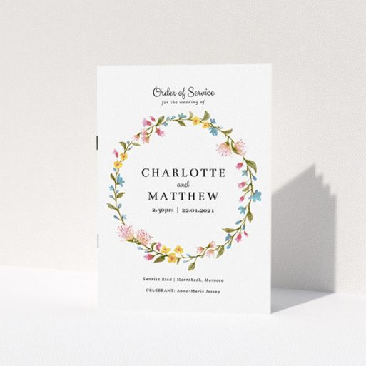 """A multipage wedding order of service template titled """"Spring Wedding Wreath"""". It is an A5 booklet in a portrait orientation. """"Spring Wedding Wreath"""" is available as a folded booklet booklet, with mainly pink colouring."""