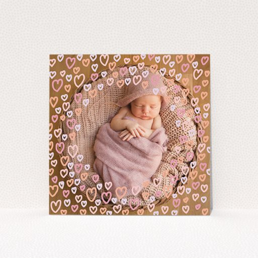 """A new baby announcement card design named """"Pink Hearts"""". It is a square (148mm x 148mm) card in a square orientation. It is a photographic new baby announcement card with room for 1 photo. """"Pink Hearts"""" is available as a flat card, with mainly light pink colouring."""