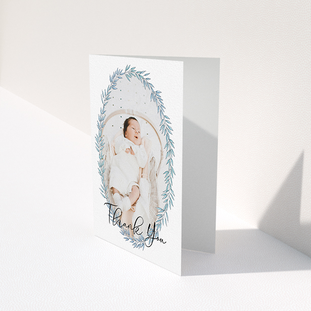 """A new baby thank you card called """"Tussled Wreath"""". It is an A6 card in a portrait orientation. It is a photographic new baby thank you card with room for 1 photo. """"Tussled Wreath"""" is available as a folded card, with tones of blue and white."""
