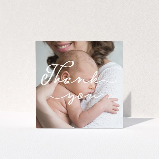 """A new baby thank you card design named """"White Thank You"""". It is a square (148mm x 148mm) card in a square orientation. It is a photographic new baby thank you card with room for 1 photo. """"White Thank You"""" is available as a folded card, with mainly white colouring."""