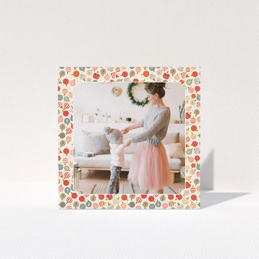 """A personalised christmas card called """"Bauble Photo"""". It is a square (148mm x 148mm) card in a square orientation. It is a photographic personalised christmas card with room for 1 photo. """"Bauble Photo"""" is available as a folded card, with tones of pink, red and light blue."""