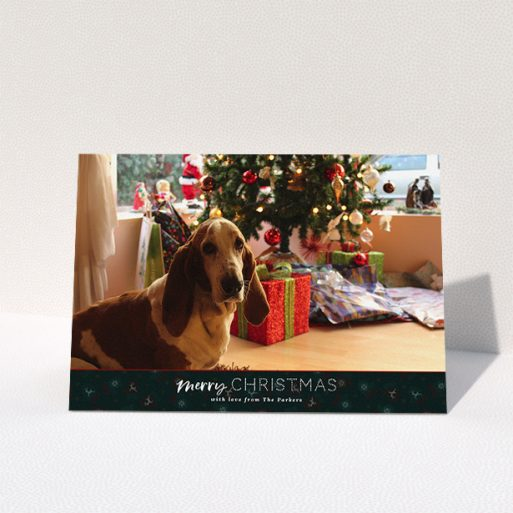 """A personalised christmas card named """"Bottom of the Stocking"""". It is an A5 card in a landscape orientation. It is a photographic personalised christmas card with room for 1 photo. """"Bottom of the Stocking"""" is available as a folded card, with tones of dark green and red."""