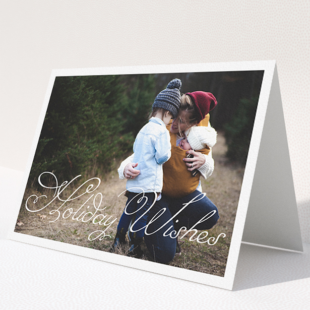 """A personalised christmas card called """"Holiday Wishes"""". It is an A5 card in a landscape orientation. It is a photographic personalised christmas card with room for 1 photo. """"Holiday Wishes"""" is available as a folded card, with mainly white colouring."""