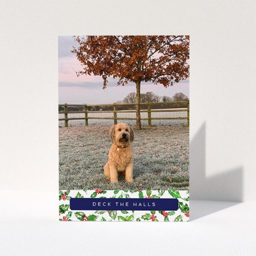 """A personalised christmas card design named """"Holly Bottom"""". It is an A5 card in a portrait orientation. It is a photographic personalised christmas card with room for 1 photo. """"Holly Bottom"""" is available as a folded card, with tones of navy blue, red and green."""