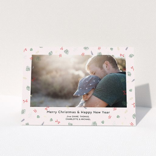 """A personalised christmas card design named """"Noeliage"""". It is an A5 card in a landscape orientation. It is a photographic personalised christmas card with room for 1 photo. """"Noeliage"""" is available as a folded card, with tones of light pink, green and light blue."""