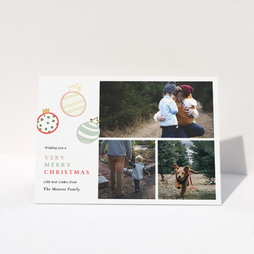 """A personalised christmas card named """"Pastel Baubles"""". It is an A5 card in a landscape orientation. It is a photographic personalised christmas card with room for 3 photos. """"Pastel Baubles"""" is available as a folded card, with tones of white and green."""