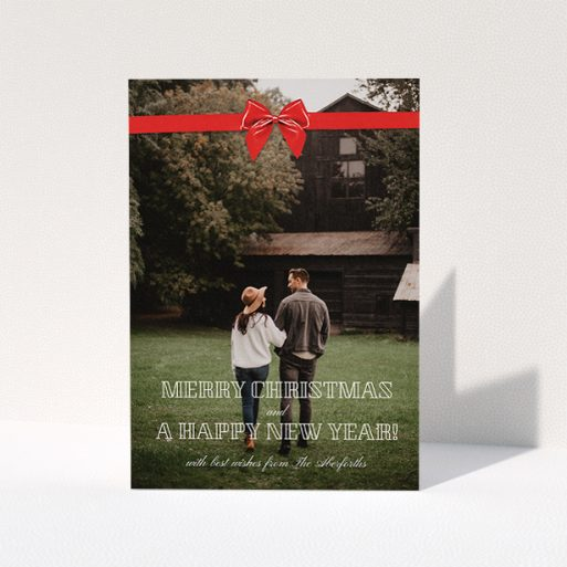 """A personalised christmas card called """"Under the Tree"""". It is an A5 card in a portrait orientation. It is a photographic personalised christmas card with room for 1 photo. """"Under the Tree"""" is available as a folded card, with mainly red colouring."""