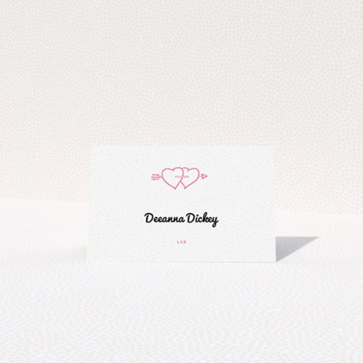 """A table place card named """"Shot to the Hearts"""". It is an 85 x 55mm card in a landscape orientation. """"Shot to the Hearts"""" is available as a folded card, with tones of white and pink."""