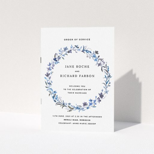 """A wedding order of service design titled """"Blue Wildflower"""". It is an A5 booklet in a portrait orientation. """"Blue Wildflower"""" is available as a folded booklet booklet, with tones of light blue, purple and grey."""