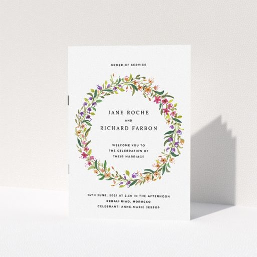"""A wedding order of service named """"Spring Wildflower"""". It is an A5 booklet in a portrait orientation. """"Spring Wildflower"""" is available as a folded booklet booklet, with tones of light green and orange."""