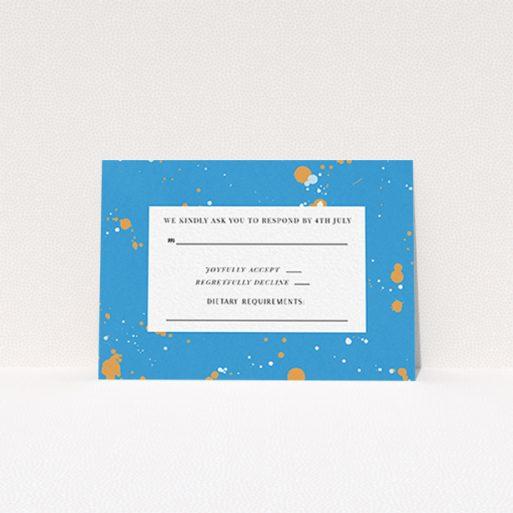 """A wedding rsvp card design named """"Orange Splatters"""". It is an A7 card in a landscape orientation. """"Orange Splatters"""" is available as a flat card, with tones of light blue and orange."""