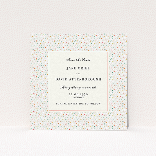 """A wedding save the date card named """"A hint of confetti"""". It is a square (148mm x 148mm) card in a square orientation. """"A hint of confetti"""" is available as a flat card, with tones of light cream and green."""