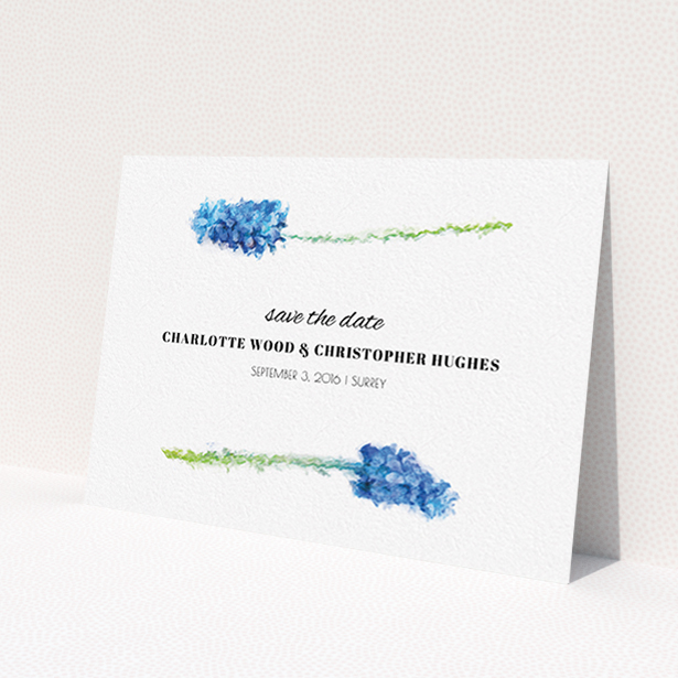 """A wedding save the date card called """"A new bloom"""". It is an A6 card in a landscape orientation. """"A new bloom"""" is available as a flat card, with tones of blue and white."""