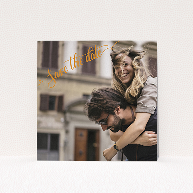 """A wedding save the date card named """"Corner Typography Photo"""". It is a square (148mm x 148mm) card in a square orientation. It is a photographic wedding save the date card with room for 1 photo. """"Corner Typography Photo"""" is available as a flat card, with mainly light orange colouring."""