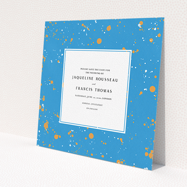 """A wedding save the date card called """"Orange Splatters"""". It is a square (148mm x 148mm) card in a square orientation. """"Orange Splatters"""" is available as a flat card, with tones of light blue and orange."""
