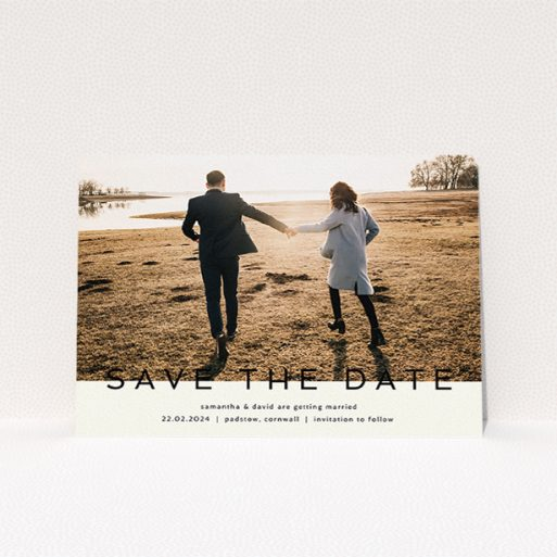 """A wedding save the date card called """"Simple Saving"""". It is an A5 card in a landscape orientation. It is a photographic wedding save the date card with room for 1 photo. """"Simple Saving"""" is available as a flat card, with tones of cream and black."""