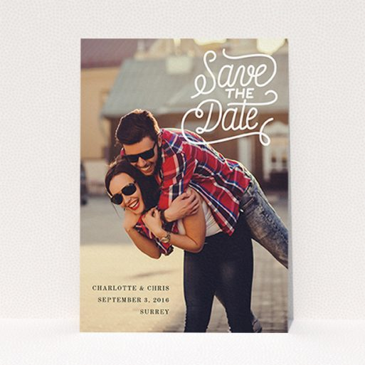 """A wedding save the date design called """"Curly Typography Photo"""". It is an A6 save the date in a portrait orientation. It is a photographic wedding save the date with room for 1 photo. """"Curly Typography Photo"""" is available as a flat save the date, with mainly white colouring."""