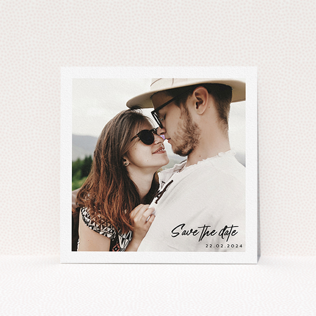 """A wedding save the date called """"Script Corner"""". It is a square (148mm x 148mm) save the date in a square orientation. It is a photographic wedding save the date with room for 1 photo. """"Script Corner"""" is available as a flat save the date, with mainly white colouring."""