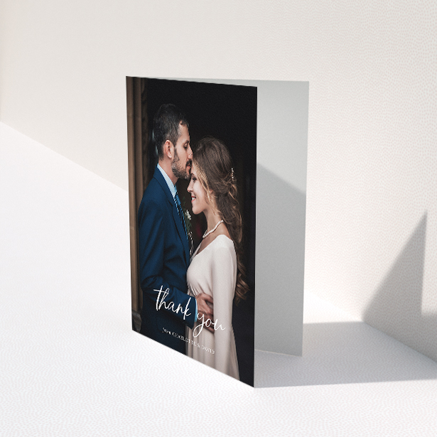 """A wedding thank you card design titled """"Calligraphy Thanks"""". It is an A5 card in a portrait orientation. It is a photographic wedding thank you card with room for 1 photo. """"Calligraphy Thanks"""" is available as a folded card, with mainly white colouring."""