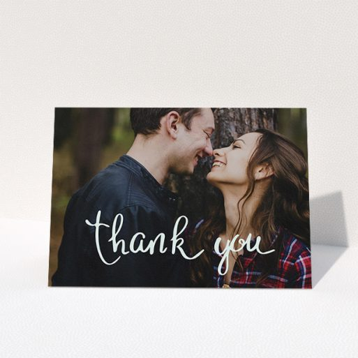 """A wedding thank you card design named """"Curly thank you"""". It is an A5 card in a landscape orientation. It is a photographic wedding thank you card with room for 1 photo. """"Curly thank you"""" is available as a folded card, with mainly white colouring."""