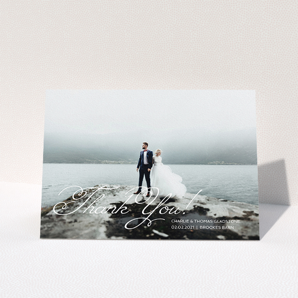 """A wedding thank you card named """"Flourished Thank You"""". It is an A5 card in a landscape orientation. It is a photographic wedding thank you card with room for 1 photo. """"Flourished Thank You"""" is available as a folded card, with mainly white colouring."""