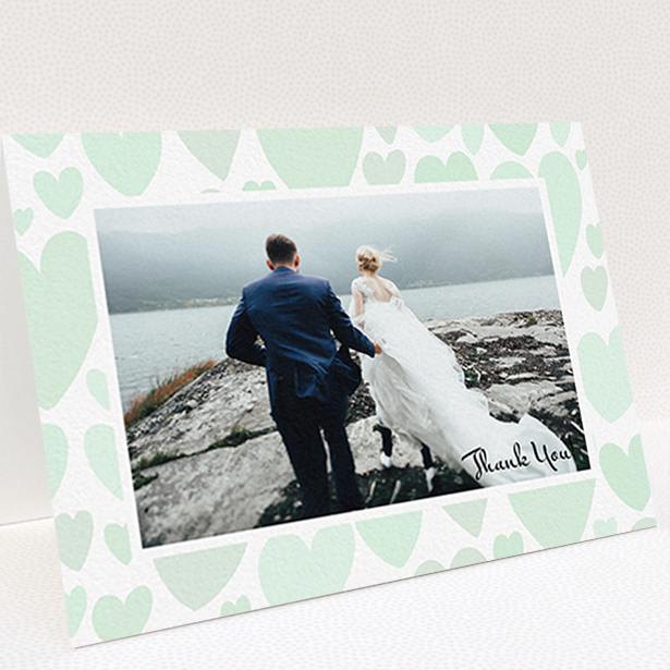 """A wedding thank you card design named """"Mint Heart Frame"""". It is an A6 card in a landscape orientation. It is a photographic wedding thank you card with room for 1 photo. """"Mint Heart Frame"""" is available as a folded card, with tones of green and white."""