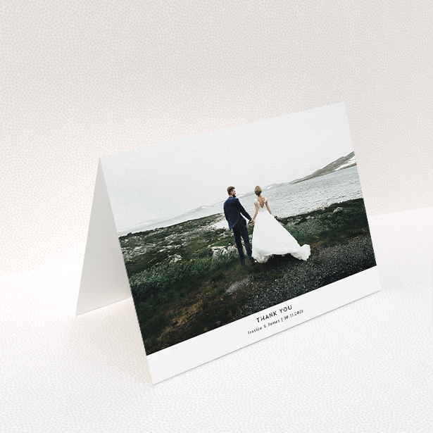 """A wedding thank you card named """"Sans Serif"""". It is an A5 card in a landscape orientation. It is a photographic wedding thank you card with room for 1 photo. """"Sans Serif"""" is available as a folded card, with mainly white colouring."""