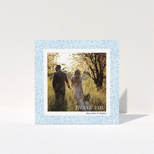 """A wedding thank you card design called """"Surrounded by flowers"""". It is a square (148mm x 148mm) card in a square orientation. It is a photographic wedding thank you card with room for 1 photo. """"Surrounded by flowers"""" is available as a folded card, with tones of blue and white."""