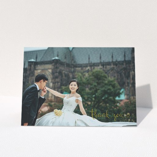 """A wedding thank you card design titled """"Thank you with a heart"""". It is an A5 card in a landscape orientation. It is a photographic wedding thank you card with room for 1 photo. """"Thank you with a heart"""" is available as a folded card, with mainly gold colouring."""