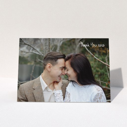 """A wedding thank you card template titled """"Thank You XOXO"""". It is an A5 card in a landscape orientation. It is a photographic wedding thank you card with room for 1 photo. """"Thank You XOXO"""" is available as a folded card, with mainly white colouring."""
