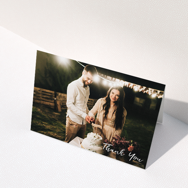 """A wedding thank you card named """"Thanks From The Corner"""". It is an A5 card in a landscape orientation. It is a photographic wedding thank you card with room for 1 photo. """"Thanks From The Corner"""" is available as a folded card, with mainly white colouring."""
