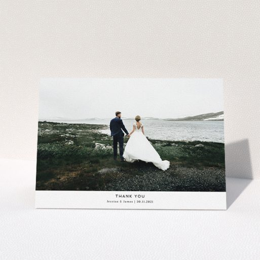 """A wedding thank you card called """"THE Wedding Photo Thank You"""". It is an A5 card in a landscape orientation. It is a photographic wedding thank you card with room for 1 photo. """"THE Wedding Photo Thank You"""" is available as a folded card, with mainly white colouring."""