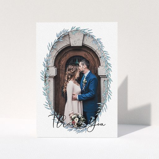 """A wedding thank you card design named """"Tussled Wreath Frame"""". It is an A6 card in a portrait orientation. It is a photographic wedding thank you card with room for 1 photo. """"Tussled Wreath Frame"""" is available as a folded card, with mainly blue colouring."""